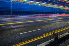 Blurred tail lights and traffic lights on road Stock Photo