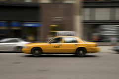 Blurred taxi speeding on city street Royalty Free Stock Photo