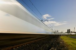A blurred time lapse of a train travelling across the frame on a curve. stock photo