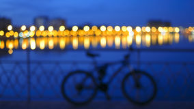 Blurred toned background with blurred city lights with reflection in river and bike silhouette by the bridge fence Stock Photo