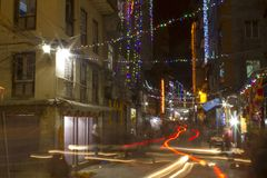 A Blurred traffic lights on the night street in the Diwali festival with a multitude of glowing colored garlands royalty free stock photo