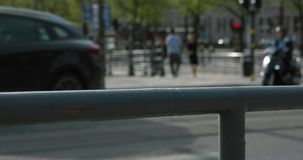 Blurred traffic and people walking on a bridge in central Stockholm on a sunny afternoon. Slow motion shot in 4K. stock video footage