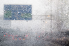 Blurred traffic on road during hard rainy day with rain drops sp Royalty Free Stock Image