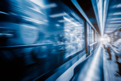 Blurred train at night leaving station in China Stock Image
