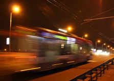 The blurred trolleybus in the evening. The motion of a blurred trolleybus in the street in the evening royalty free stock image