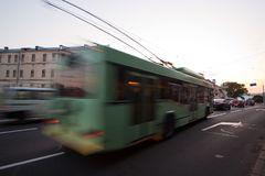 A blurred trolleybus on the street. The motion of a blurred trolleybus on the street at dusk royalty free stock photos