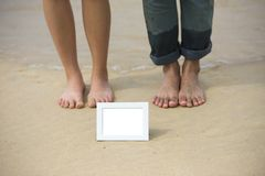 Blurred two feet of couple with white empty picture frame. Blurred two feet of asian couple with white empty picture frame on clear beach sand in sunny day stock photos