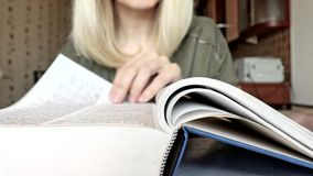 Blurred unrecognizable blond woman leafing a big book, leading a finger on pages and reading.  stock video