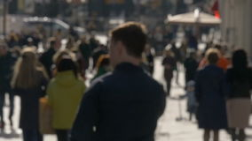 Blurred unrecognizable people walk along sunny spring street slow motion video stock footage