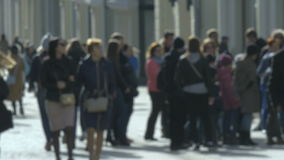 Blurred unrecognizable people walk along sunny spring street stock footage