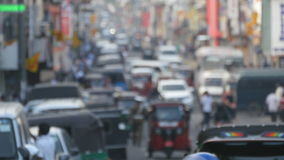 Blurred unrecognizable people are walking around city center. Cars drive on roads in the town. Out of focus is backdrop. Of bustling big city with busy traffic stock footage