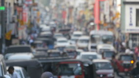 Blurred unrecognizable people are walking around city center. Cars drive on roads in the town. Out of focus is backdrop. Of bustling big city with busy traffic stock video footage