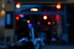 Blurred us chopper motorbike in front of bistro and pub neon lights at evening. Blurred bistro and pub neon lights at evening in city mall of south germany royalty free stock image