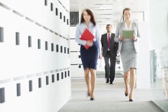Blurred view of businesswomen walking in office Royalty Free Stock Photos