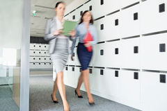 Blurred view of businesswomen walking in office royalty free stock photography