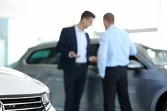 Blurred view of car dealership with salesman and client, closeup. Blurred view of car dealership with salesman and client stock photos