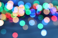 Blurred view of Christmas lights. On color background stock images