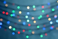 Blurred view of Christmas lights on color background stock photo