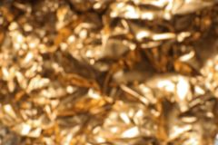 Blurred view of crumpled golden foil. As background stock photo