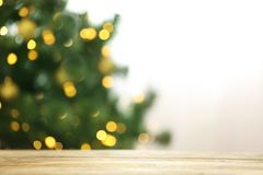 Blurred view of fir tree with glowing Christmas lights table indoors. Festive mood stock photography