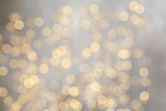 Blurred view of golden Christmas lights as background. Bokeh effect royalty free stock photography