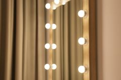 Blurred view of makeup mirror near wall in dressing room. Space for text royalty free stock photo