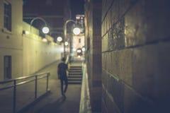 Blurred view of man walking on dark street stock photo