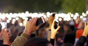 A blurred view of many bright smartphone flashlights filling