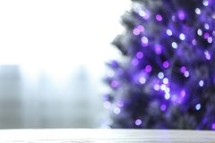 Free Blurred View Of Beautiful Christmas Tree With Purple Lights Near Window Indoors, Focus On Wooden Table. Space For Text Royalty Free Stock Image - 163107996