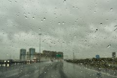 Blurred view of road traffic on a rainy day through the car window stock images