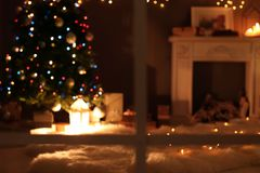 Blurred view of stylish living room interior with Christmas lights and fireplace. At night through window stock images