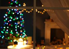 Blurred view of stylish living room interior Christmas lights and fireplace at night through window. Blurred view of stylish living room interior with Christmas royalty free stock image