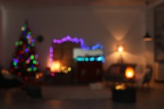 Blurred view of stylish living room interior with Christmas lights. At night stock photo