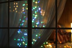 Blurred view of stylish living room interior with Christmas lights. At night through window Royalty Free Stock Photos