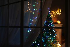 Blurred view of stylish living room interior with Christmas lights. At night through window stock image