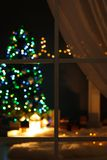 Blurred view of stylish living room interior with Christmas lights. At night through window stock photography