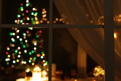 Blurred view of stylish living room interior with Christmas lights. At night through window royalty free stock photo