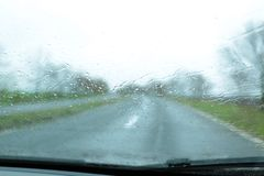 Blurred view of suburban road through wet car window. Rainy weather royalty free stock photography