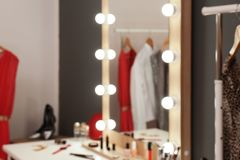 Blurred view of table with makeup products and mirror near grey wall. In dressing room stock image