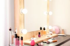 Blurred view of table with makeup products and mirror near white wall, closeup. Dressing room royalty free stock photography