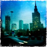 Blurred view of Warsaw at night. Blurred image of Warsaw at night taken with mobile phone. Moving car on left and the Palace of Culture on the right, the city's Royalty Free Stock Images