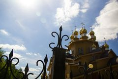 Blurred view on the wooden cathedral and sky from behind the fence stock photography