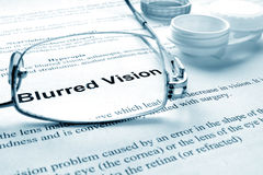 Blurred vision. Paper with words  blurred vision, glases and container for lenses. Eye disorders Royalty Free Stock Photo