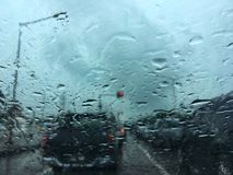 Blurred water drop on the car glass background, blurred of outside road and traffic view through car window. Blurred water drop on the car glass background royalty free stock images