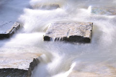 Blurred water. Flow round stones Royalty Free Stock Photo