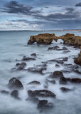 Blurred water like milk on rocks on beach in Albufeira. Royalty Free Stock Images