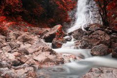 Sarika big waterfall with autumn colors. Blurred waterfall of Sarika National Park, Nakhon Nayok, Thailand. Autumn red foliage leaf by color process. Nature Royalty Free Stock Photography