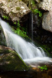 Blurred waterfall. Waterfall between some rock and vegetation in the mountain Stock Images