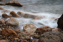 Blurred waves on wet stones of seacoast in off-season Stock Image