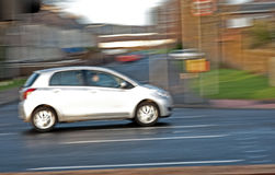 Blurred white car driving in town. A panned image of a small white car driving on a road  with motion blurring captured in an urban environment Stock Images
